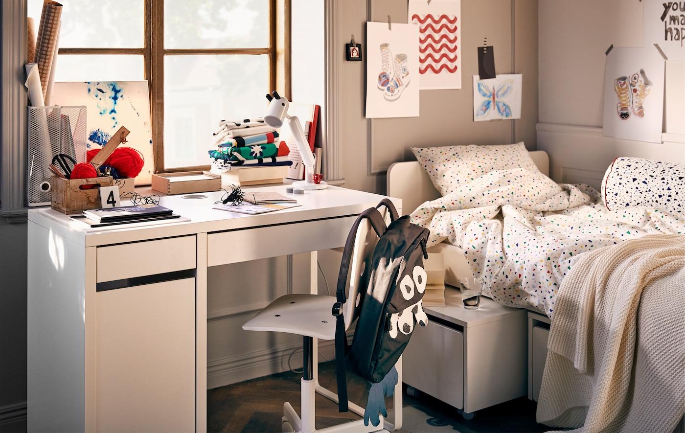 Intérieur de chambre d'enfant avec un lit, de l'art mural et un espace de travail avec un bureau MICKE, une chaise pivotante et une lampe KRUX.