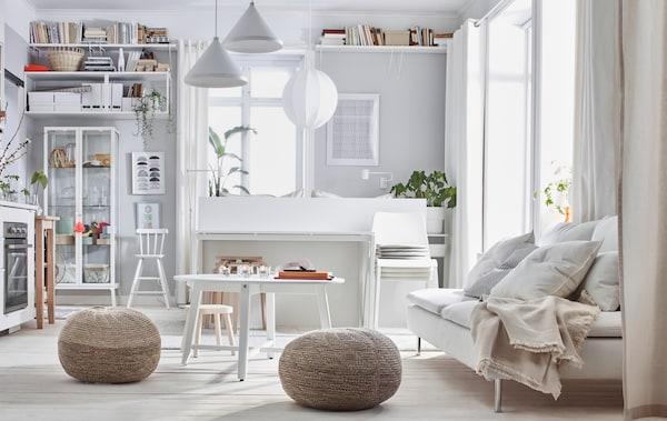 Intérieur d'un appartement d'une pièce avec une combinaison de couleurs pâles: lit, canapé, cuisinette, rangement et deux poufs SANDARED.