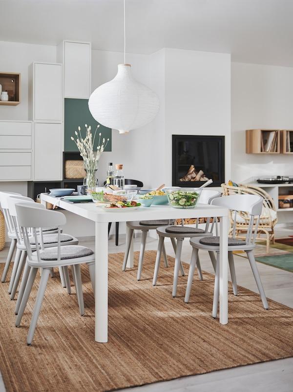 Interioare de cameră de zi și sufragerie combinate, cu șemineu, corpuri de depozitare suspendate și o masă TINGBY cu scaune OMTÄNKSAM.