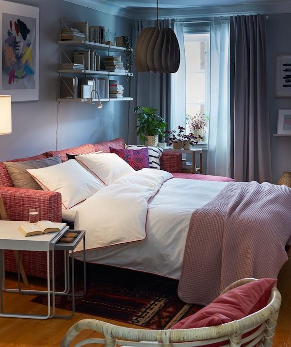 Interior de un salón con sofá cama en el modo de cama de matrimonio. A su alrededor: mesas anidadas, sillas y una librería de pared con libros.