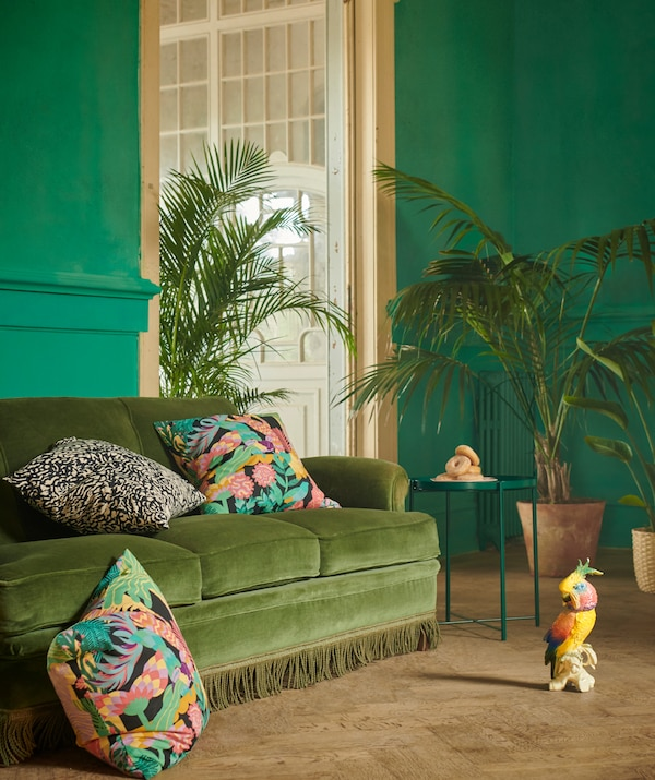Interior in elegant style and shades of green. Big plants by a sofa with GRIMHILD and NÄBBFLY cushions placed in it.