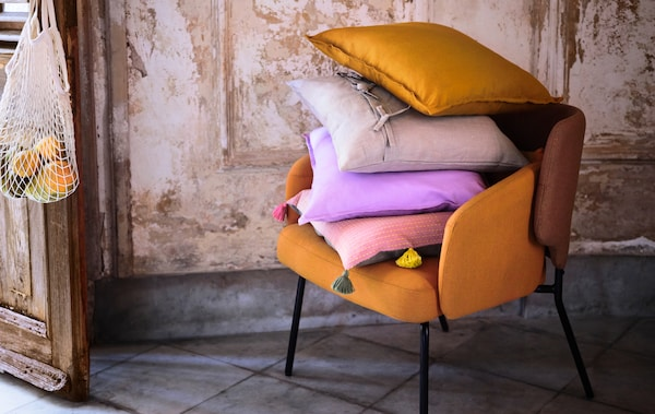 Interior in refined but rough natural materials. An armchair holds a pile of cushions – one of them with a KLARAFINA cover.