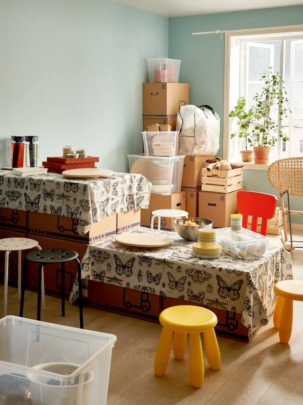 Interior in the middle of moving in. JÄTTENE boxes stacked to form a two-level table set for a simple meal, seating around it.