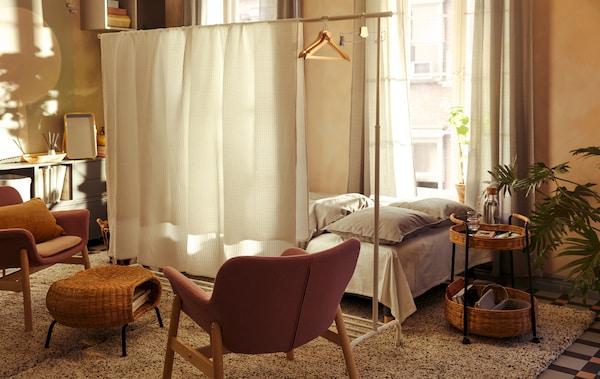 Interiorul unei camere de zi unde un pat mare se află în spatele unui separator de cameră improvizat dintr-un suport de haine RIGGA și așternuturi VÅRELD.