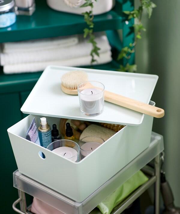 Інтер'єр ванної кімнати з візком з аксесуарами, зверху — KUGGIS КУГГІС коробка з набором для ванної: масла, щітки, SINNLIG СІНЛІГ свічки.