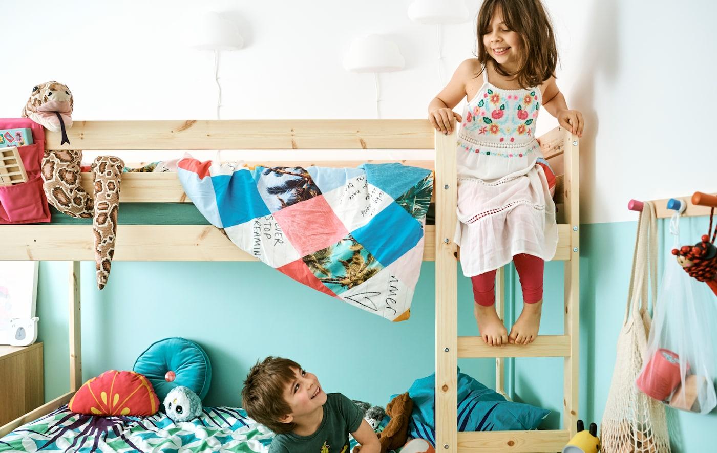Într-o cameră de copii, un băiat stă în patul de jos al unui pat supraetajat și se uită în sus la sora lui, care stă pe scara patului.