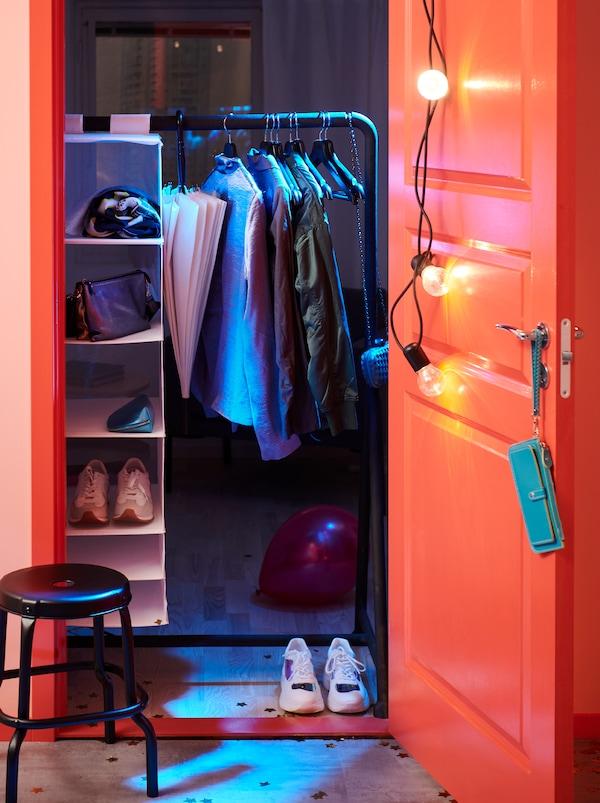 Intrarea într-o cameră. Imediat în interiorul ei se vede un cuier mare BUMERANG, haine și o unitate de depozitare SKUBB agățată de acesta.