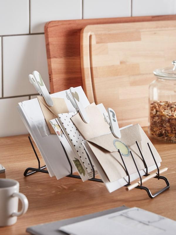Între accesorii de bucătărie împrăștiate, un suport de farfurii RINNIG așezat orizontal este folosit ca suport pentru plicuri și hârtii.