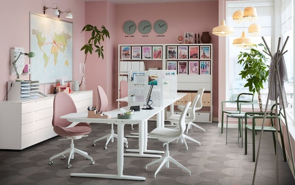 Iroda, rózsaszín falakkal és ülő/álló BEKANT íróasztallal, fehér színben és ergonomikus HATTEFJÄLL forgószékekkel, világosbarna-rózsaszín színben.