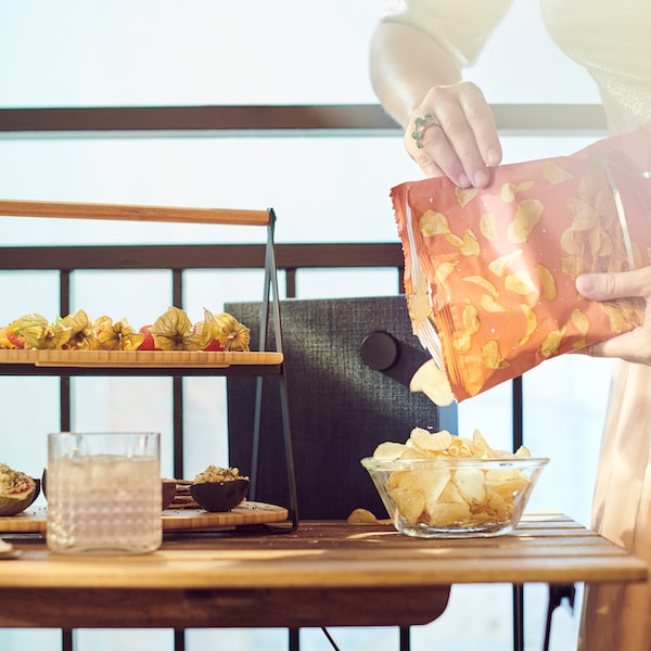 いろいろな軽食を盛り付けたサービングトレイがあるテーブルの上のボウルにポテトチップスを注いでいる手。