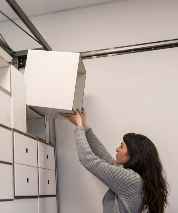 "is_ikea/democratic_design/201544_tidd04a_04_PH128524.jpg"" alt=""Female in grey sweater placing a white storage unit into a wall made out of many storage units."
