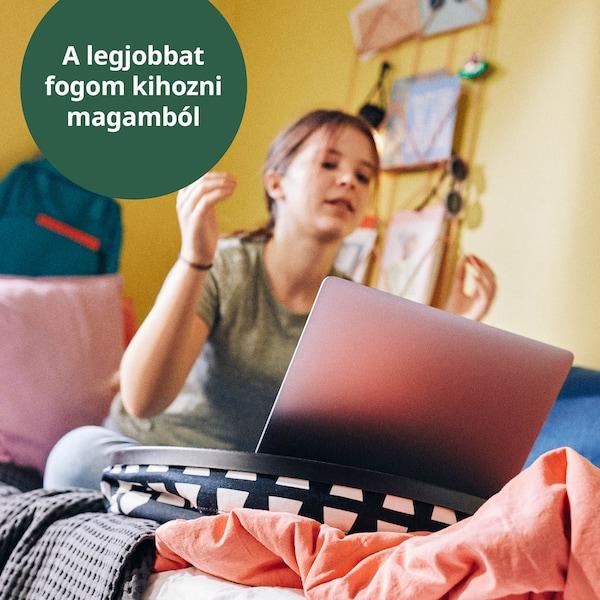 Iskolás gyerek az ágyán ülve tanul a számítógépén, BYLLAN laptoptartóval.