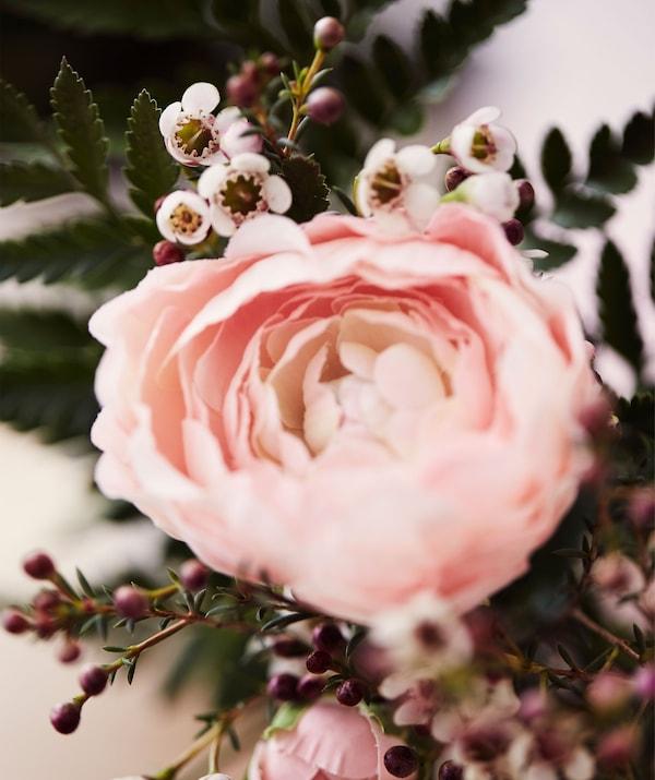 Искусственный розовый цветок лютика и листья.
