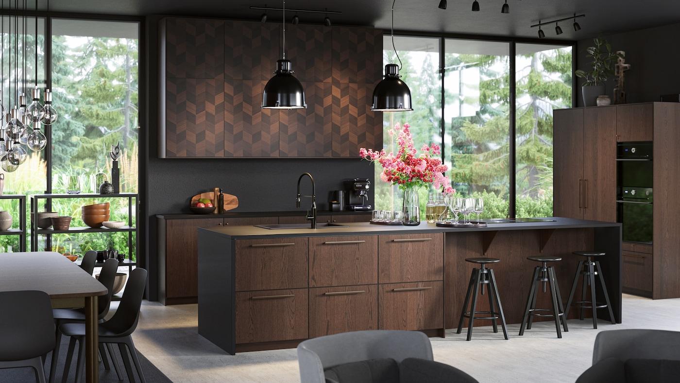 Isla de cocina grande y elegante con frentes de madera. Taburetes altos negros, lámparas de techo negras y una nevera con puertas de madera.