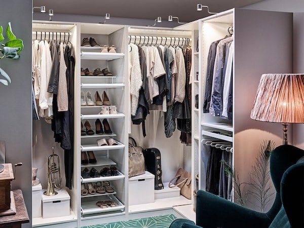 Iso vaatekaappi jossa on paljon kenkiä hyllyillä ja paljon vaatteita roikkumassa henkareissa. Vaatekaappikokonaisuus on valaistu.
