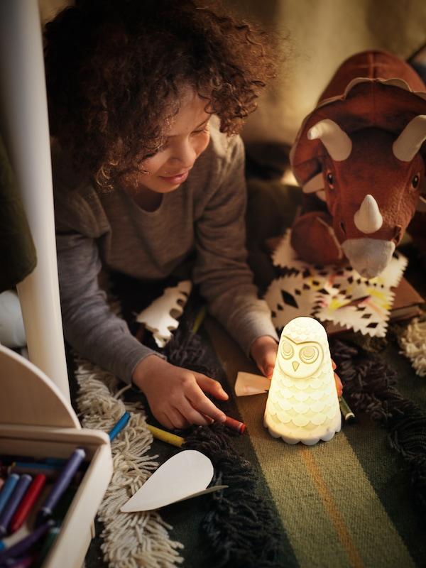 Ispod stola dečak se igra SOLBO noćnim svetlom koje obasjava njegovo lice i njegovu igračku dinosaurusa.