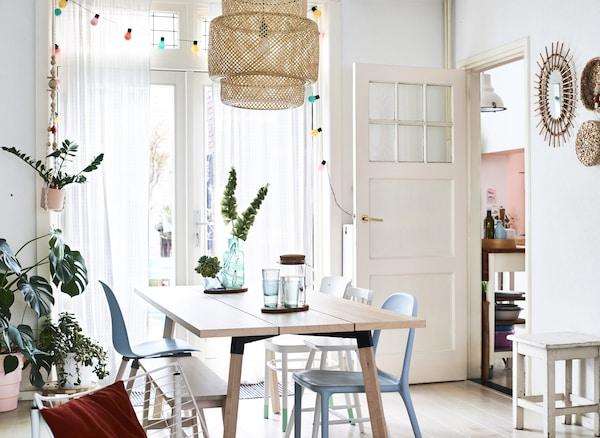 白い壁と淡い色調の木製テーブルがそばにあるダイニングテーブル。