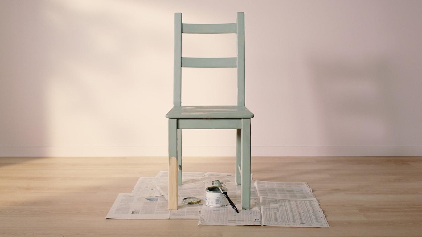 페인트 한 통과 페인트붓과 함께 신문지 위에 놓여 있고 한쪽 다리 절반을 제외하고 그린 색상으로 칠해진 IVAR 이바르 소나무 의자.