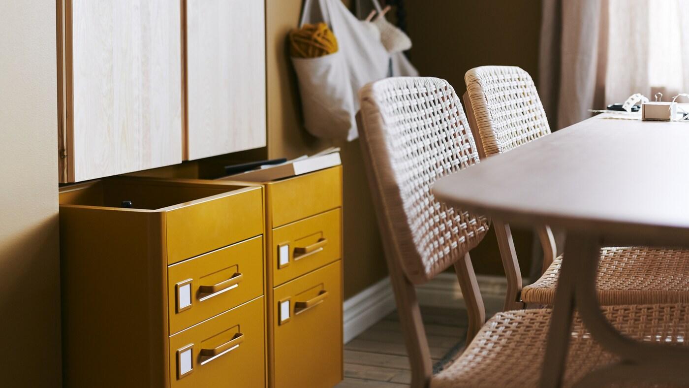 ตู้ IVAR/อิวาร์ ติดผนังและตู้ลิ้นชัก IDÅSEN/อิดัวเซน มีล้อ, โต๊ะกับเก้าอี้สองตัว และกระเป๋าแขวนอยู่ที่ผนังด้านหลัง