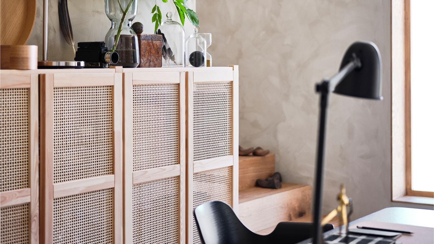 IVAR ІВАР шафа із дверцятами з ротангу з особистими речами зверху. Серед нею стоїть стілець.
