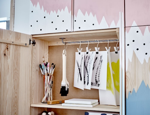 IVAR خزائن مع صورة مرسومة عليها باللون الأزرق، والأبيض والوردي. مفتوحة لإظهار مساحة التخزين في الداخل.