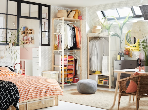 IVAR pine shelving unit in a bedroom with lots of open storage and white protective clothing covers.