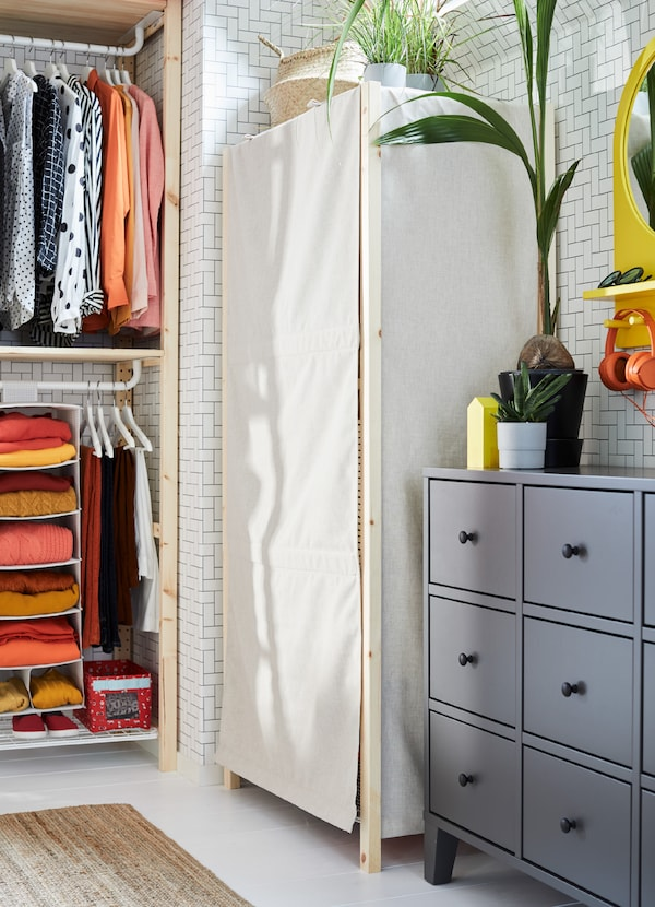 IVAR shelf with an optional pull-down beige cover to protect clothes.