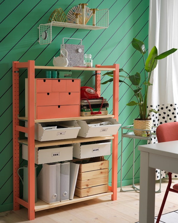 IVAR shelving unit with white drawers, a white wall shelf, white curtains and a green plant stand.