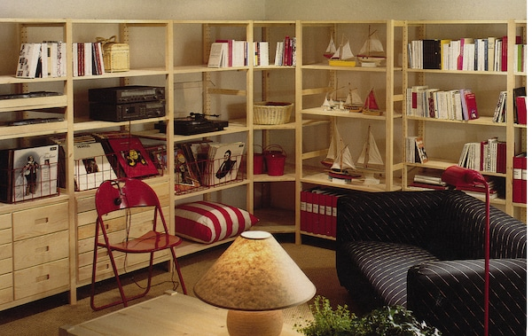 IVAR shelving units spanning two walls in an 80's themed living room.