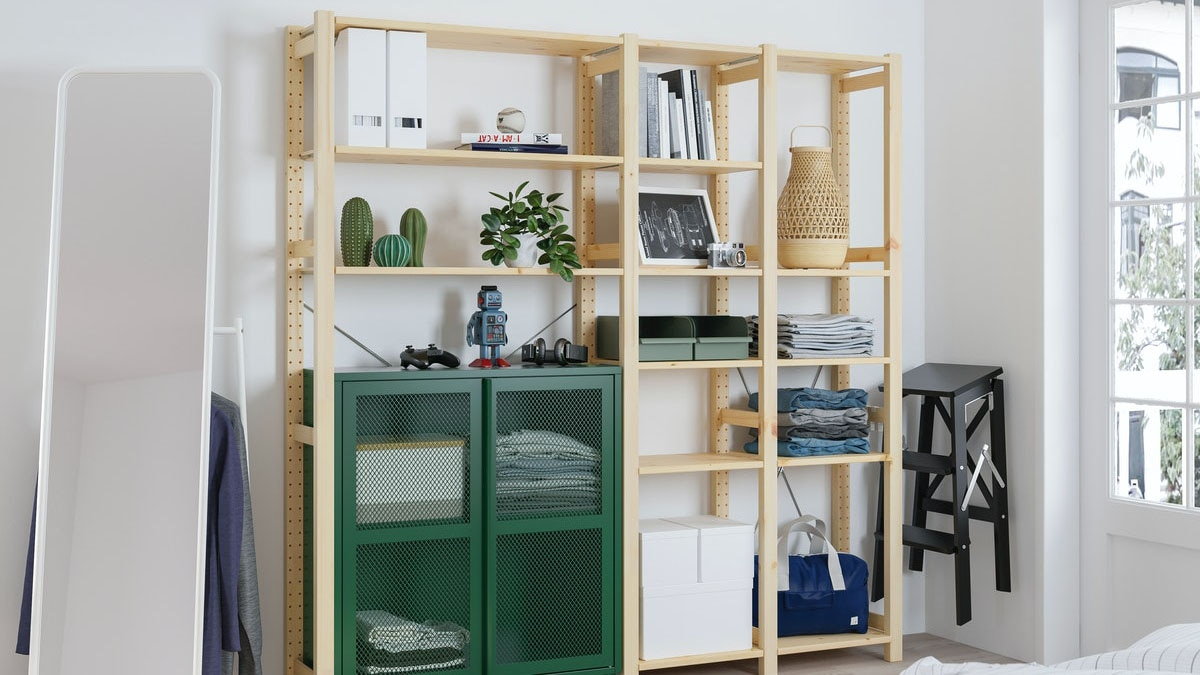 IVAR storage unit in a living room, with a mirror, stool and sofa bed.