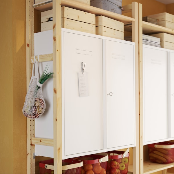 IVAR white metal cabinets on shelf sections in pine and a metal clip with a note is placed on the metal door of the cabinet.
