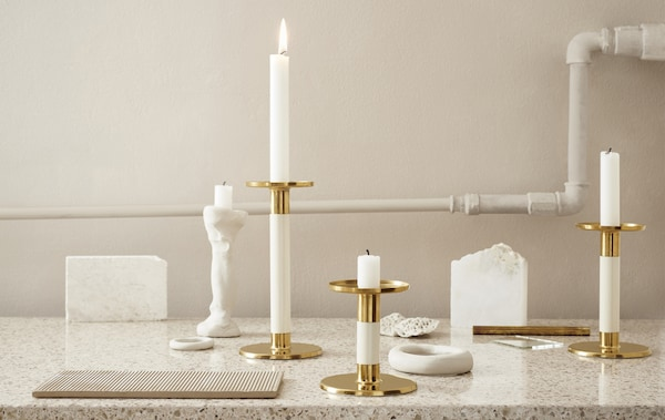 Ivory and gold-coloured candlesticks displayed on a marble worktop.