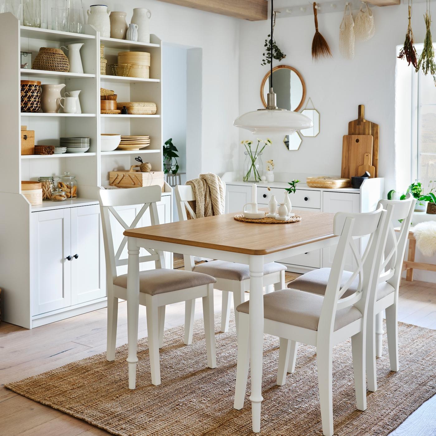 Jadalnia z białym stołem z dębowym blatem, czterema białymi krzesłami, jutowym dywanem i dwoma białymi, dwudrzwiowymi, wysokimi szafkami.