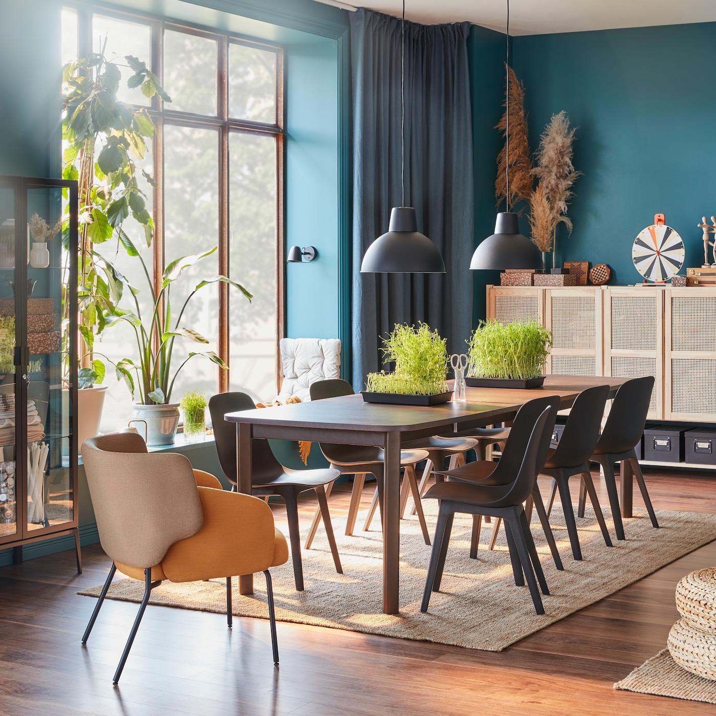 Jadalnia z dużym, ciemnobrązowym stołem, ośmioma antracytowymi krzesłami, żółtym fotelem i szafkami z bambusowymi drzwiami.
