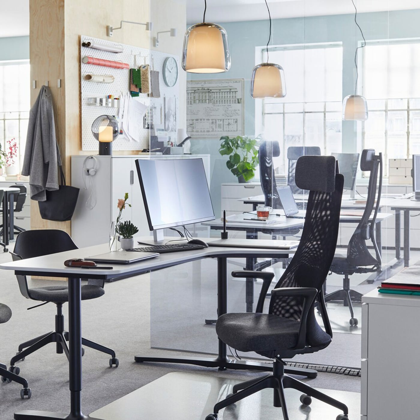 JÄRVFJÄLLET adjustable black work chairs and smooth BEKANT white sit-stand desks arranged in an open and airy office space.