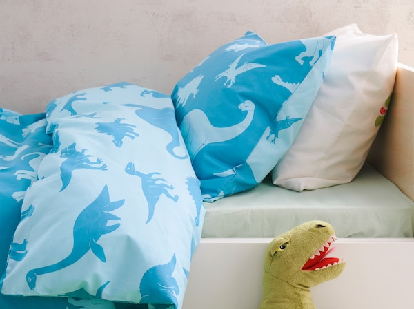 JÄTTELIK quilt cover in blue with a dinosaur print on both sides lying in a bed with a soft toy dinosaur sticking up.