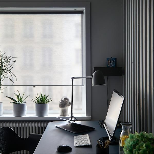 Janelas num escritório em casa com estore de correr SKOGSKLÖVER em cinzento quase fechado, por trás de uma secretária com um candeeiro e um monitor de computador.