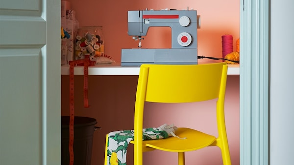 JANINGE chair yellow in front of a desk with a sewing machine on the top.