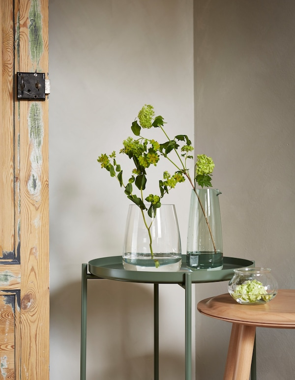 Jarrones BERÄKNA y VILJESTARK sobre una mesa, con una única planta y un esqueje verde que demuestran que las cosas sencillas pueden ser bonitas.