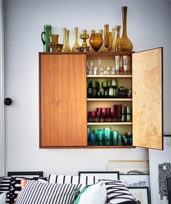 Jarrones de cristal almacenados dentro y encima de un armario de pared, y agrupados por color.