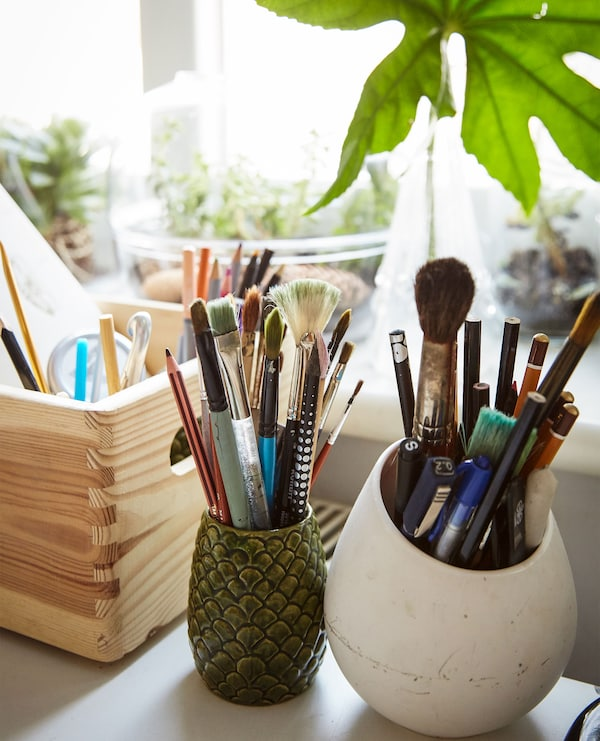 Jars and a wooden box filled with artist's brushes and pens.