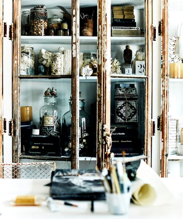 Jars and books stored inside a glass-fronted cabinet with rusty doors.