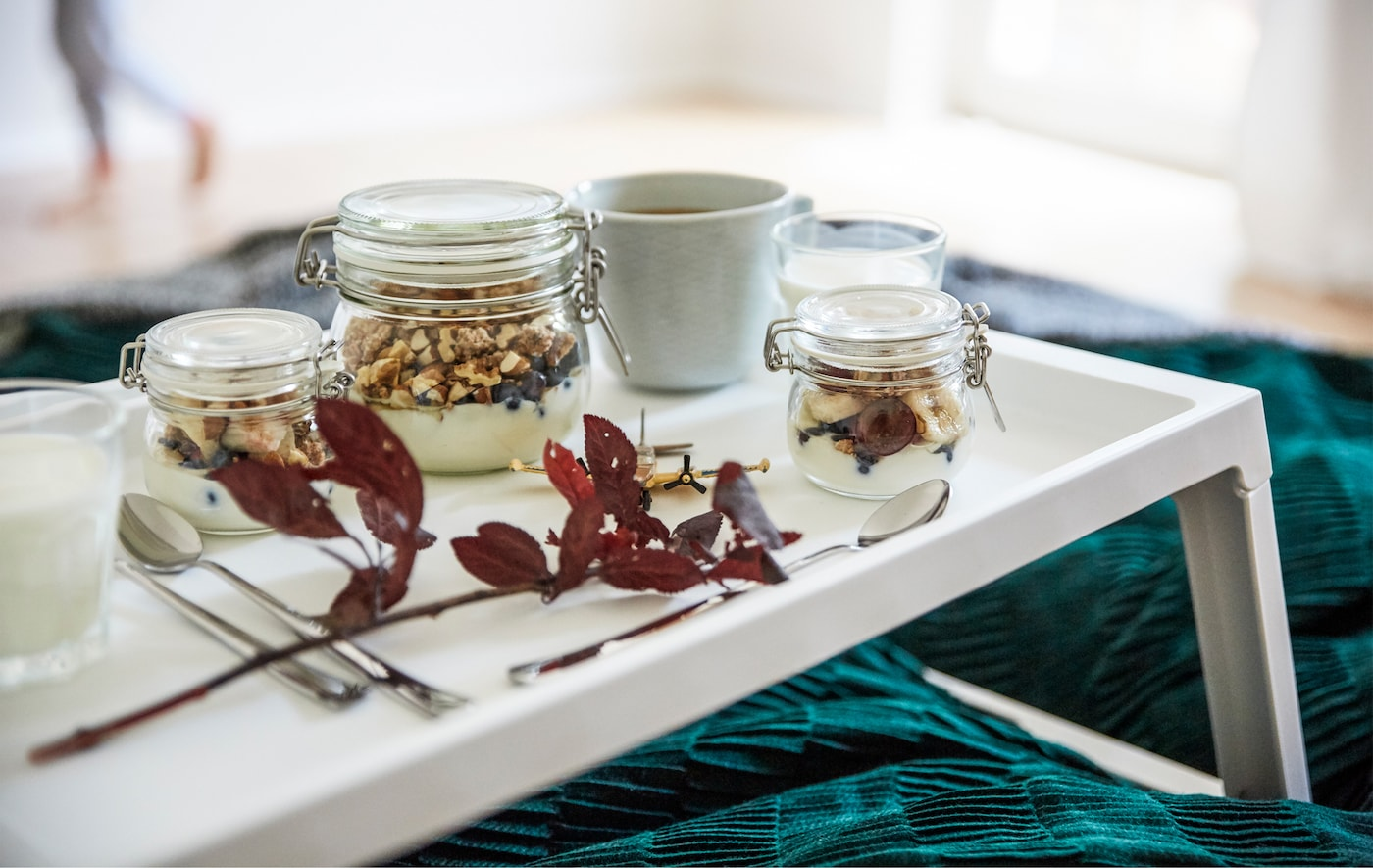Jars filled with granola and yoghurt on a white tray on a bed.