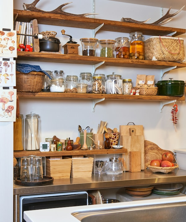Jars of ingredients and pickles on wooden shelves above a metal worktop with wooden boxes and boards.