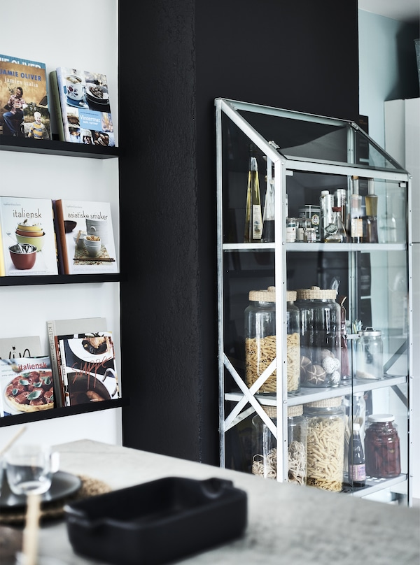 Jars of ingredients in a glass cabinet.
