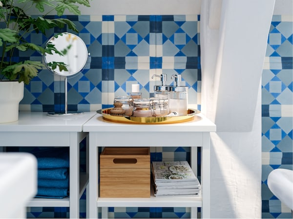 Jars, soap dispensers, a plant and a mirror on top of open white shelving units in a bathroom tiled with graphic coloured tiles.