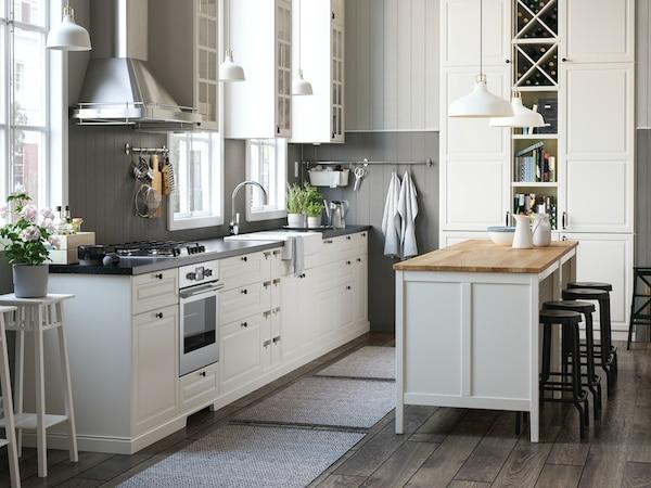 Jasna kuchnia METOD z białymi frontami BODBYN, ciemnym blatem i wyspą kuchenną.