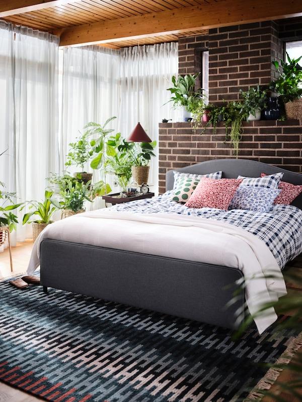 Jasna sypialnia z łóżkiem tapicerowanym HAUGA, wielobarwnym dywanem RESENSTAD i mnóstwem zielonych roślin.