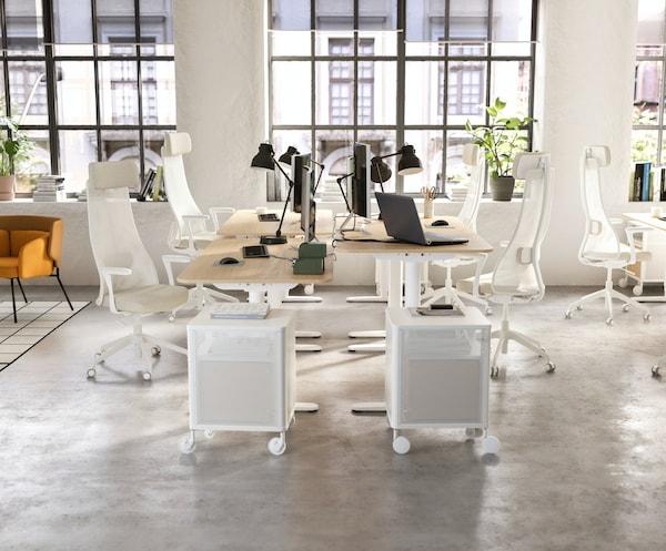 Jasna, urządzona na otwartym planie przestrzeń biurowa z czterema zestawionymi ze sobą biurkami BEKANT, białymi krzesłami biurowymi i czarnymi lampami biurkowymi.