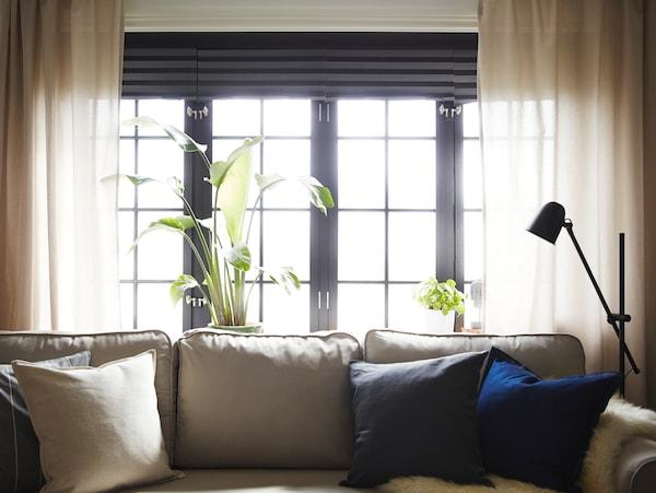 Jasnobeżowa rozkładana sofa ustawiona pod czterema oknami z beżowymi zasłonami i ciemnoszarymi, plisowanymi roletami zaciemniającymi.